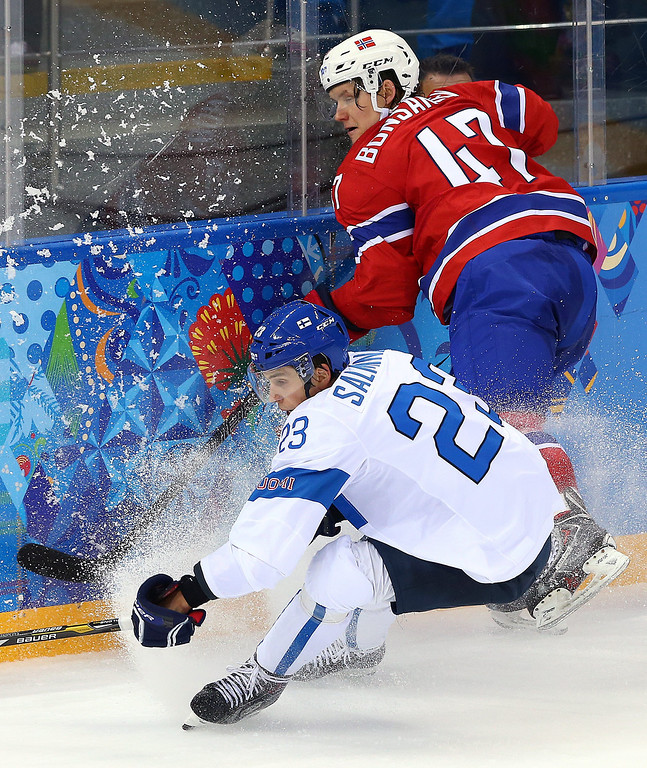 . Sakari Salminen (L) of Finland fights for the puck with Alexsander Bonsaksen (R) of Norway during the match between Norway and Finland at the Shayba Arena in the Ice Hockey tournament at the Sochi 2014 Olympic Games, Sochi, Russia, 14 February 2014.  EPA/SRDJAN SUKI