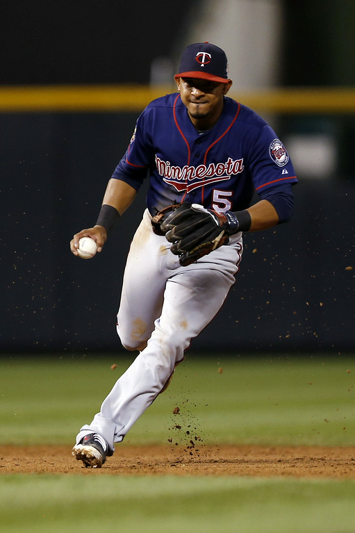 . Minnesota Twins shortstop Eduardo Escobar looks to throw out Colorado Rockies\' Justin Morneau at first during the eighth inning of a baseball game on Friday, July 11, 2014, in Denver. (AP Photo/Jack Dempsey)