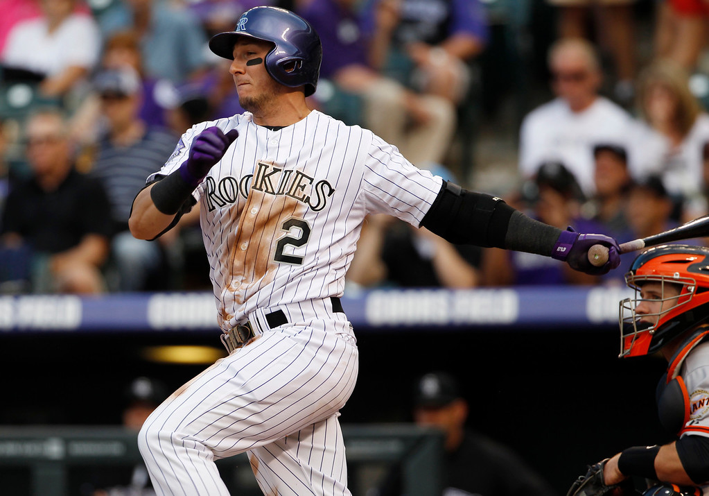 . Colorado Rockies\' Troy Tulowitzki, left, grounds out as San Francisco Giants catcher Buster Posey looks on to end the first inning of a baseball game in Denver, Saturday, May 18, 2013. (AP Photo/David Zalubowski)