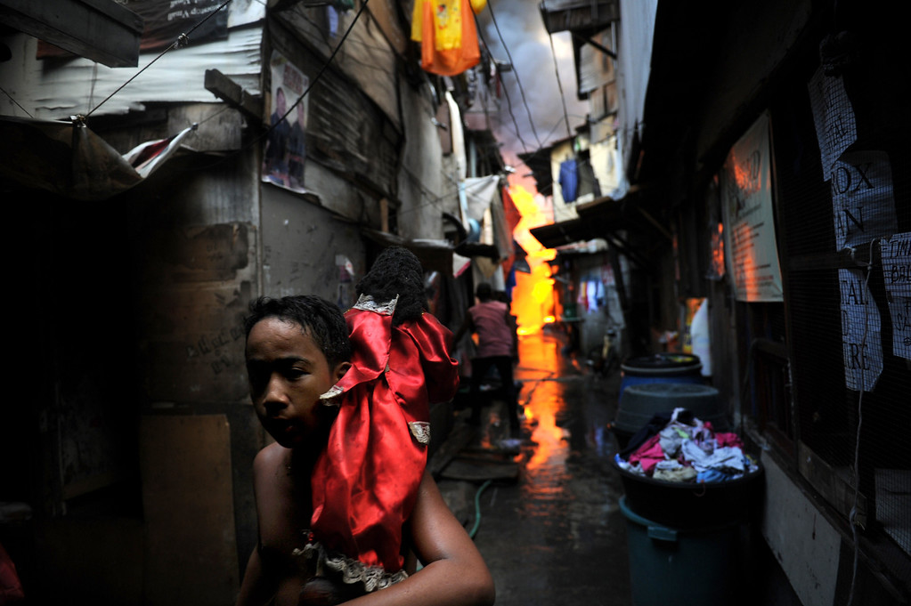 . A boy carrying a religious statue runs from burning houses after a fire engulfed a shanty town at the financial district of Manila on July 11, 2013. There were no immediate reports of casualties from the blaze, which occurred mid-morning amid government plans to relocate thousands of families living in areas vulnerable to floods and typhoons. TED ALJIBE/AFP/Getty Images