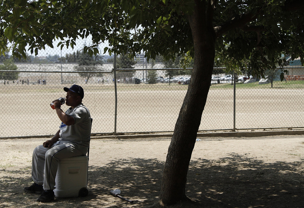 . Sunday league baseball player Alex Gallegos sips a cool drink at Sepulveda Basin Recreation Area on June 30, 2013 in Los Angeles amid a heat wave gripping the southwest US.     JONATHAN ALCORN/AFP/Getty Images