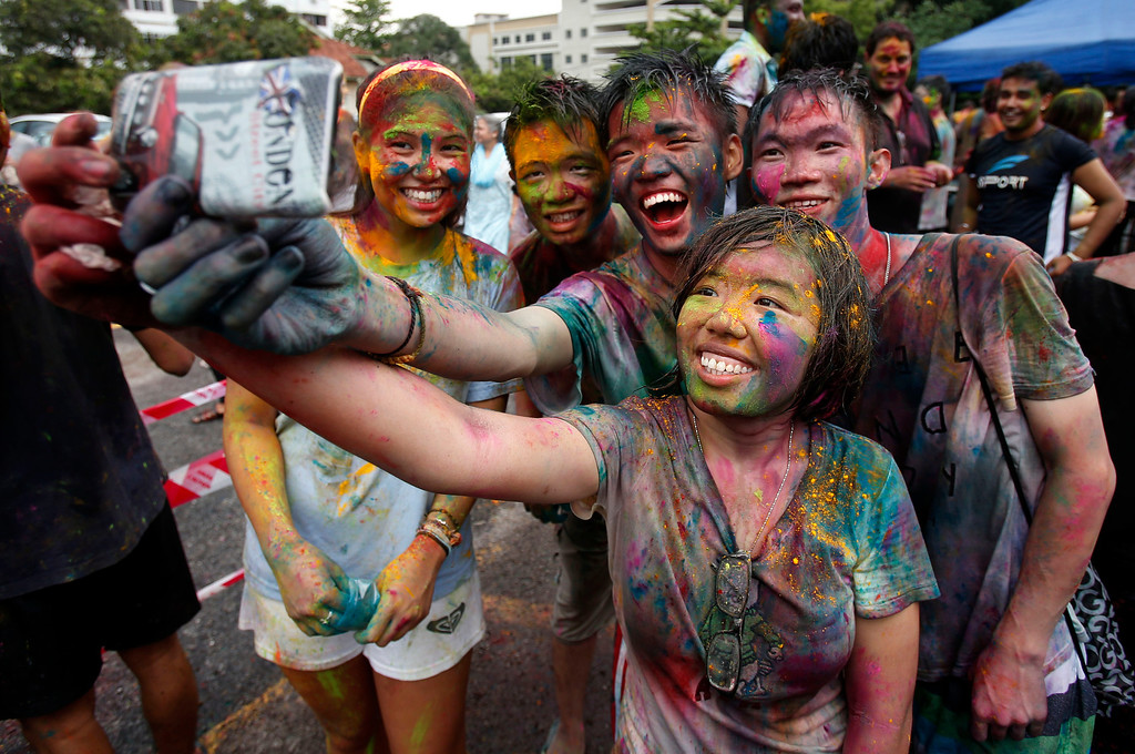 . Teenagers, faces smeared with colored powder, take a photo with a mobile phone during a religious spring festival Holi in Kuala Lumpur, Malaysia, Sunday, March 31, 2013. Holi, the Hindu festival of colors, is celebrated by people throwing colored powder and water at each other. (AP Photo/Lai Seng Sin)