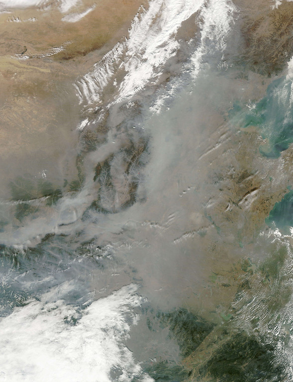 . This October 22, 2013 NASA satellite image shows smog(Grayish) over eastern China. Thick smog enveloped a major Chinese city for a third day Tuesday, with schools and a regional airport shut and poor visibility forcing ground transport to a halt in places. Images from Harbin, a northeastern city of more than 10 million people and the host of a popular annual ice festival, showed roads shrouded in smog, with visibility in some areas reduced to less than 50 meters. Flights remained severely delayed, after more than 250 flights were cancelled at the local airport on Monday, according to Chinese media. Air pollution levels were easing on Tuesday evening but remained as much as 15 times the levels deemed safe by the World Health Organization.  AFP PHOTO / NASA /HO/AFP/Getty Images