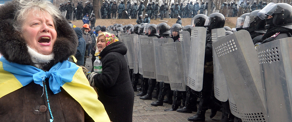 . An Ukrainian opposition activist speak to riot-forces standing guard in front of the parliament in Kiev on January 21, 2014.  AFP PHOTO/ SERGEI SUPINSKY/AFP/Getty Images