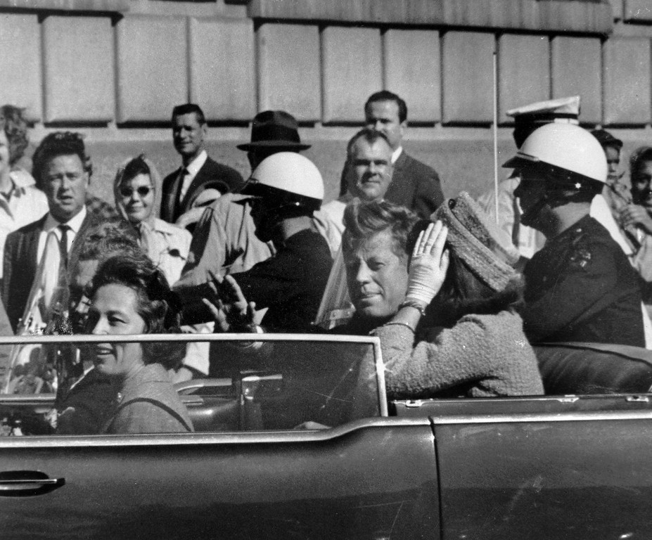 . President John F. Kennedy rides in a  motorcade approximately one minute before he was shot in Dallas on Nov. 22, 1963.  Riding with Kennedy are first lady Jacqueline Kennedy, right, Nellie Connally, left, and her husband, Gov. John Connally of Texas. Associated Press file