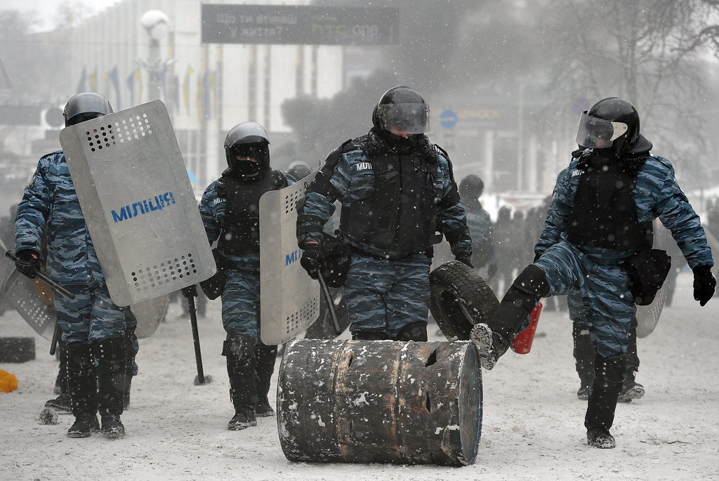. Riot policemen remove a barricade during an anti-government protest in downtown Kiev, Ukraine, 22 January 2014. Two protesters have died during violent clashes with police in Kiev, Ukrainian opposition activists said 22 January 2014.   EPA/ALEXEY FURMAN