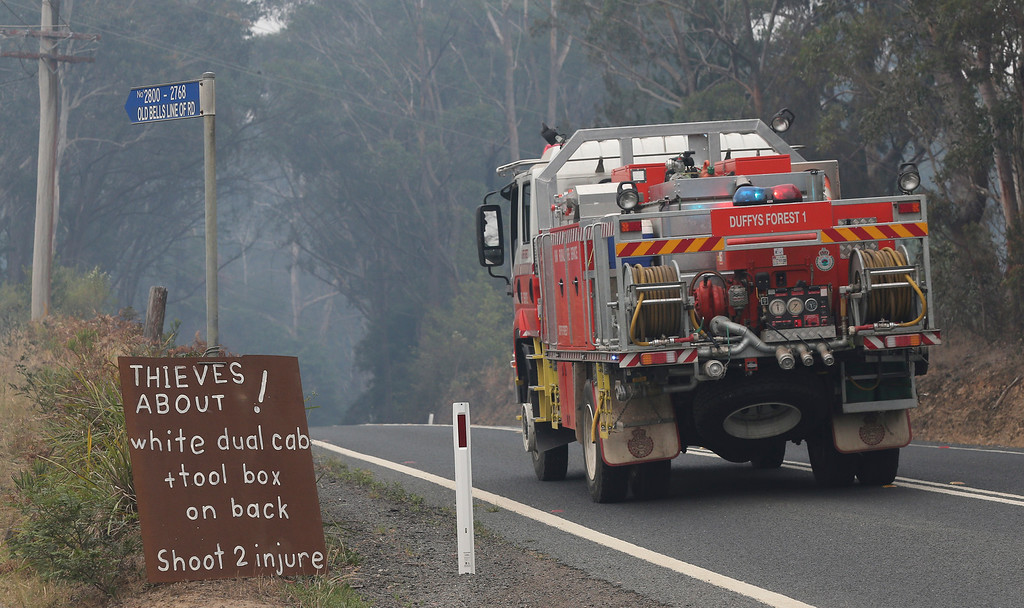 ". A firetruck drives past a roadside sign that says ""Thieves about!, white dual cab + toolbox on the back, Shoot 2 injure\""  outside Bilpin,  75 kilometers (47 miles) west of Sydney in Australia, Tuesday, Oct. 22, 2013. Authorities have warned that hotter weather and increased winds are expected and are preparing for the conditions to worsen. (AP Photo/Rob Griffith)"