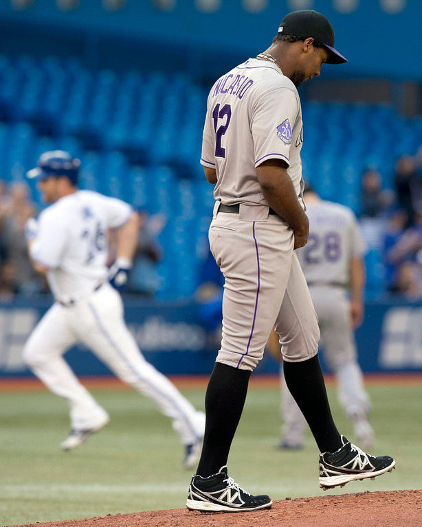 . Colorado Rockies starting pitcher Juan Nicasio walks back to the mound as Toronto Blue Jays Adam Lind rounds the bases on his three-run home run during the first inning of a baseball game in Toronto on Wednesday, June 19, 2013. (AP Photo/The Canadian Press, Frank Gunn)