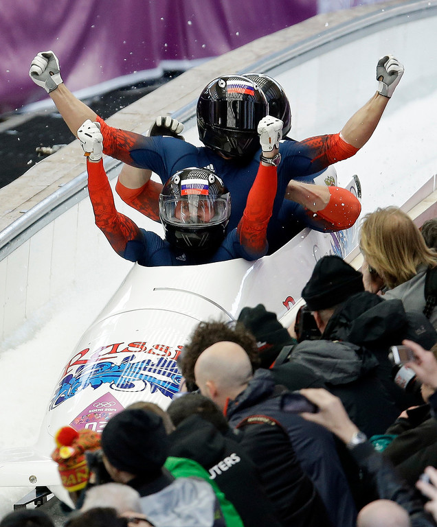 . The team from Russia RUS-1, with Alexander Zubkov, Alexey Negodaylo, Dmitry Trunenkov, and Alexey Voevoda, celebrates after they won the gold medal during the men\'s four-man bobsled competition final at the 2014 Winter Olympics, Sunday, Feb. 23, 2014, in Krasnaya Polyana, Russia. (AP Photo/Natacha Pisarenko)