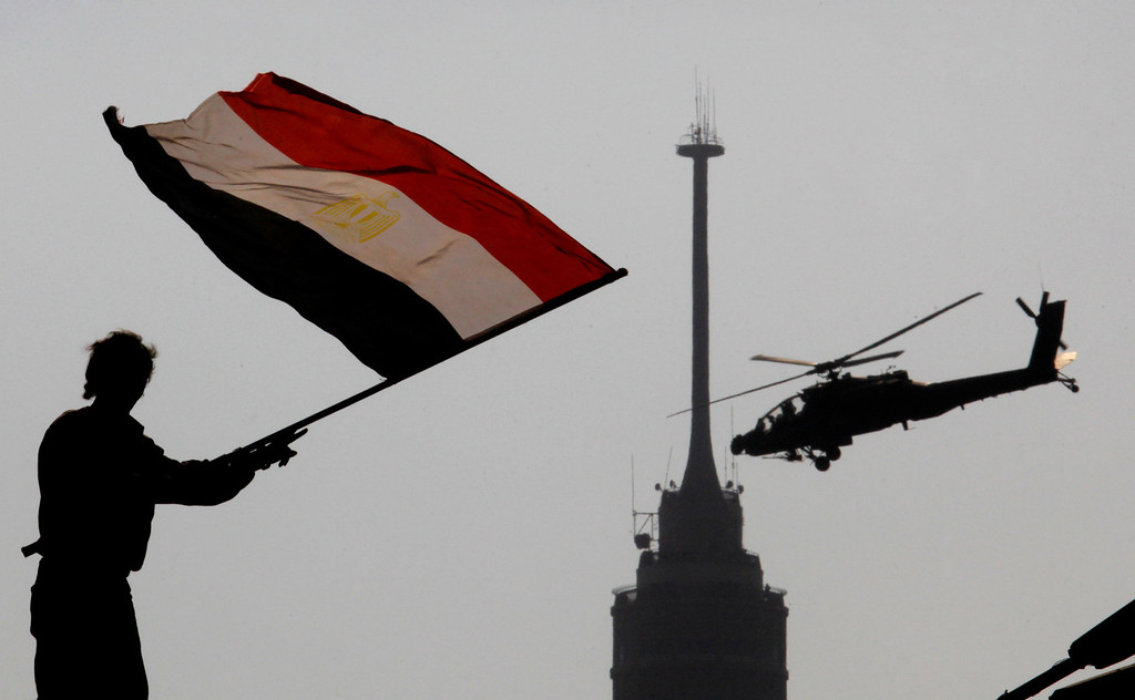 ". An opponent of Egypt\'s ousted president Mohammed Morsi waves a national flag as a military helicopter flies over Tahrir Square in Cairo, Egypt, Friday, July 5, 2013.  Egyptian troops opened fire on mostly Islamist protesters marching on a Republican Guard headquarters Friday to demand the restoration of ousted President Mohammed Morsi, killing at least one. The shooting came as tens of thousands of his supporters chanting ""down with military rule\"" rallied around the country.(AP Photo/Amr Nabil)"