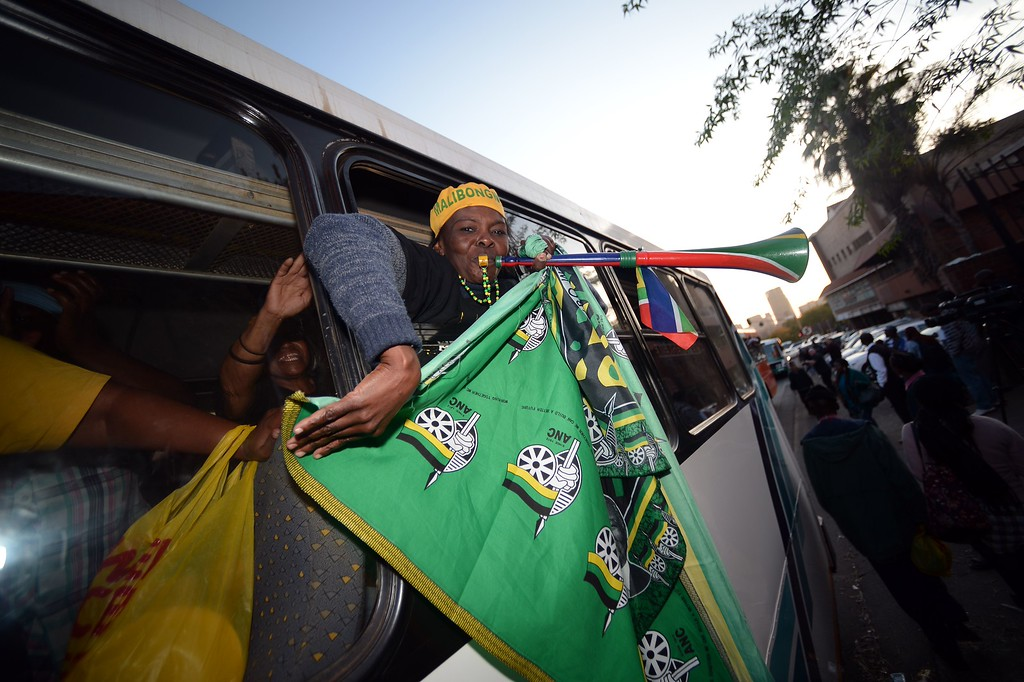 """. A woman holding an ANC party flag takes part in a gathering to support of former South African President Nelson Mandela outside the Medi Clinic Heart hospital in Pretoria on June 27, 2013. Nelson Mandela remained in critical condition today despite tentative signs of improvement, as US President led a chorus of support for the \""""hero for the world.\"""" South African President, who abruptly cancelled a trip abroad to be near the 94-year-old anti-apartheid hero, reported that he \""""remains critical but is now stable.\""""  FILIPPO MONTEFORTE/AFP/Getty Images"""