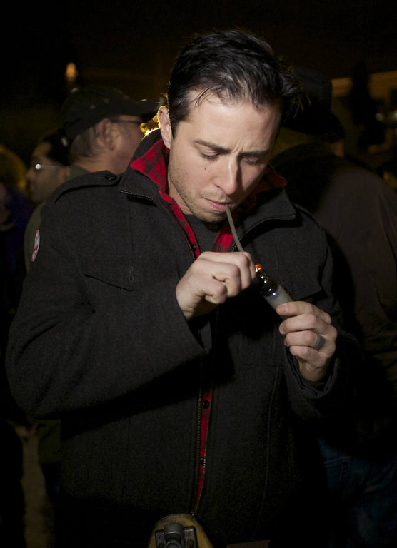 . Jared Cruver of Snohomish, Washington smokes marijuana from a mini water pipe  shortly after a law legalizing the recreational use of  marijuana took effect on December 6, 2012 in Seattle, Washington.  Voters approved an initiative to decriminalize the recreational use of marijuana making it one of the first states to do so. (Photo by Stephen Brashear/Getty Images)