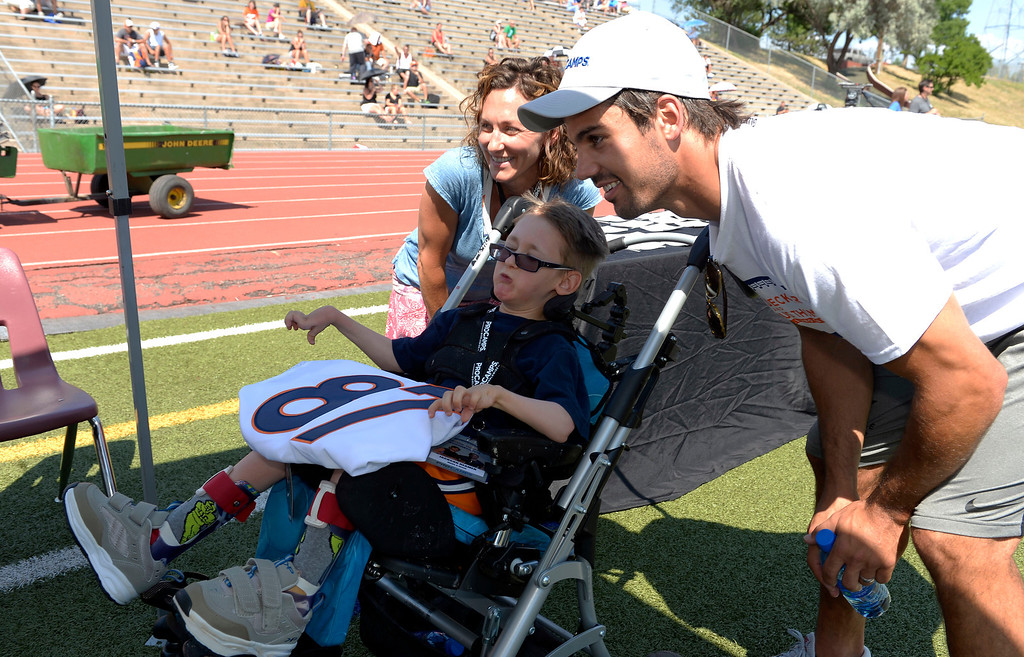 . Eric Decker poses for a photo with Jackson Reamer 12 and his mom Megan Reamer at his football camp. The meet and greet was part of Make a Wish Foundation. Demaryius Thomas and Eric Decker team up with ProCamps for their football camp held at Littleton High School July 11, 2013.(Photo By John Leyba/The Denver Post)