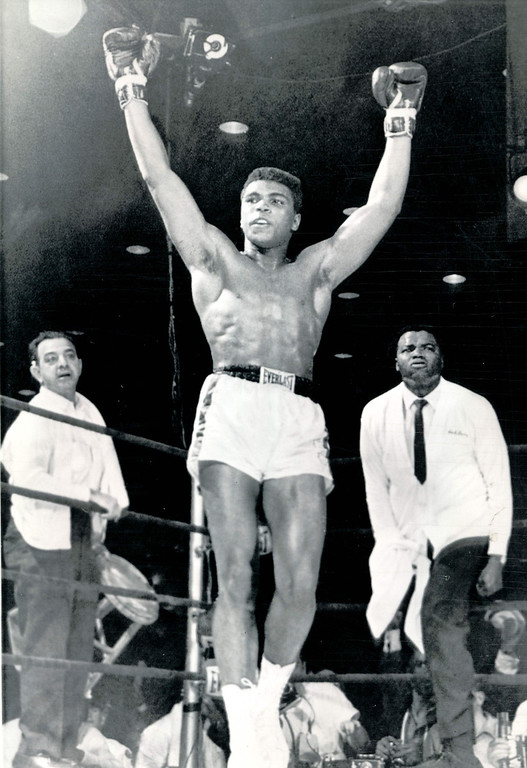 . MIAMI BEACH, Fla., Feb. 25--THE WINNER AND NEW CHAMPION--Cassius Clay raises both hands as handlers enter the ring after he was declared world champion of the heavyweight ranks in Miami Beach, Fla. tonight.  Clay stopped champion Sonny Liston after six rounds.  1964  Credit: AP