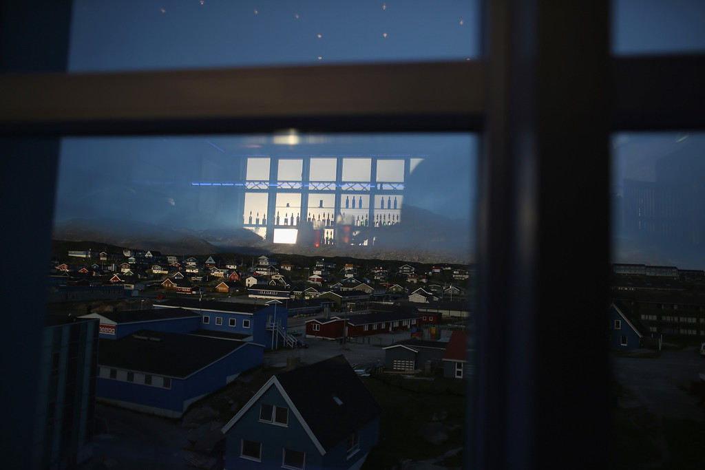. Bottles of alcohol in a bar are seen reflected in the window overlooking homes on July 28, 2013 in Nuuk, Greenland. (Photo by Joe Raedle/Getty Images)