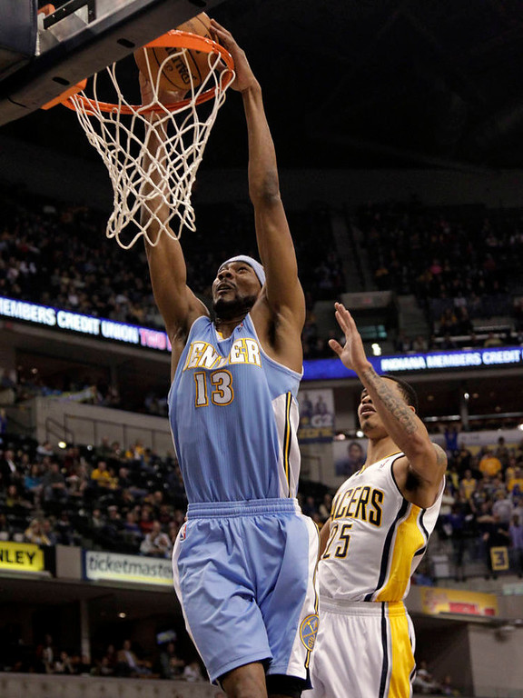 . Denver Nuggets forward Corey Brewer, left, dunks in front of Indiana Pacers forward Gerald Green during the first half of an NBA basketball game in Indianapolis, Friday, Dec. 7, 2012. (AP Photo/AJ Mast)