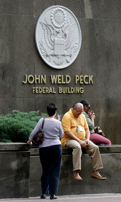 . Workers take a break outside the John Weld Peck Federal Building, Tuesday, Oct. 1, 2013, in Cincinnati. The impact of the partial federal government shutdown began rippling across Ohio on Tuesday, with a national military museum and national park closing and thousands of federal employees going on furlough. (AP Photo/Al Behrman)