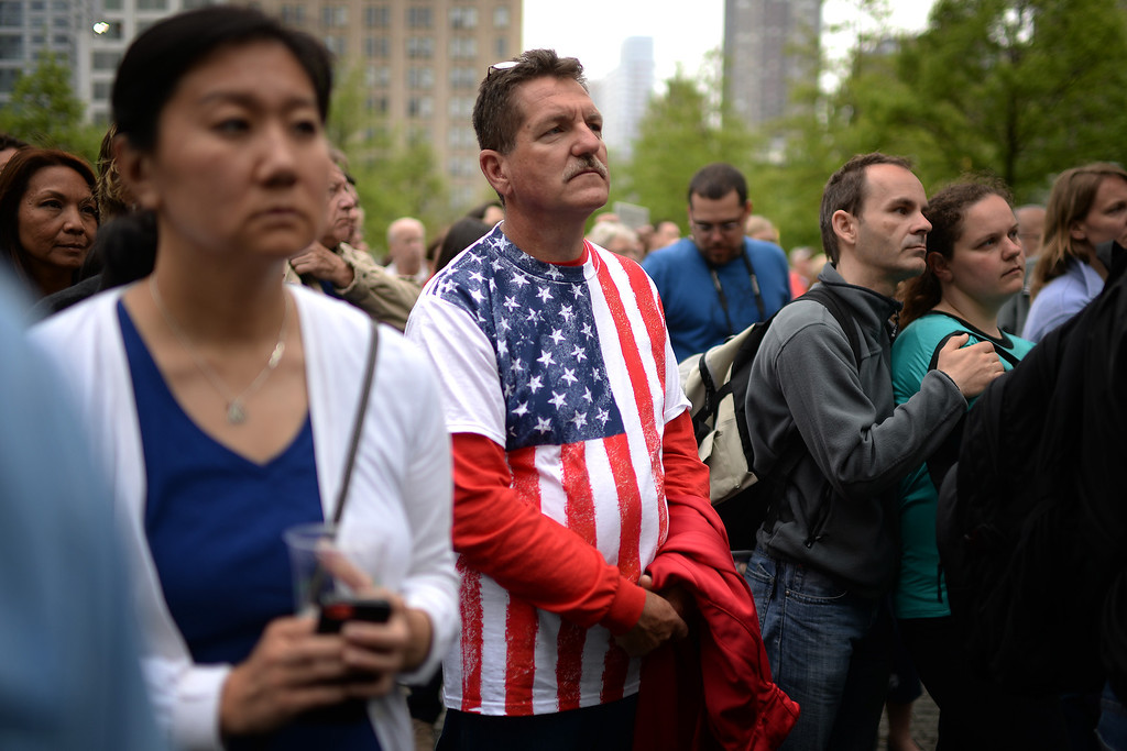 . Members of the general public watch a screen projection of U.S. President Barack Obama giving a speech during the dedication ceremony at the National September 11 Memorial Museum in New York on Thursday, May 15, 2014. (AP Photo/Anthony Behar, Pool)