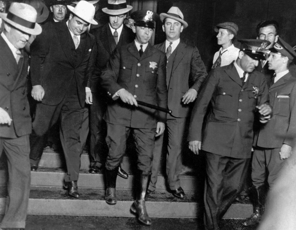 """. Alphonse \""""Al\"""" Capone, left, in white hat, as he emerged from the Federal Building after trial Dec. 10, 1931 in Chicago.  (AP Photo)"""