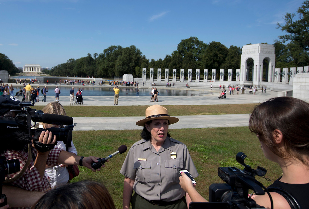 . National Park Service spokeswoman Carol Johnson speaks to reporters at the National World War II Memorial in Washington, Tuesday, Oct. 1, 2013. A group of veterans walked past barriers at the closed World War II memorial with help from members of Congress. Hundreds of veterans arrived for a previously scheduled visit to the memorial Tuesday morning to find it barricaded by the National Park Service. Members of Congress, including Republican Rep. Michele Bachmann of Minnesota, went to the site after receiving panicked emails and cut police tape to let in the veterans from Iowa and Mississippi.  (AP Photo/Carolyn Kaster)
