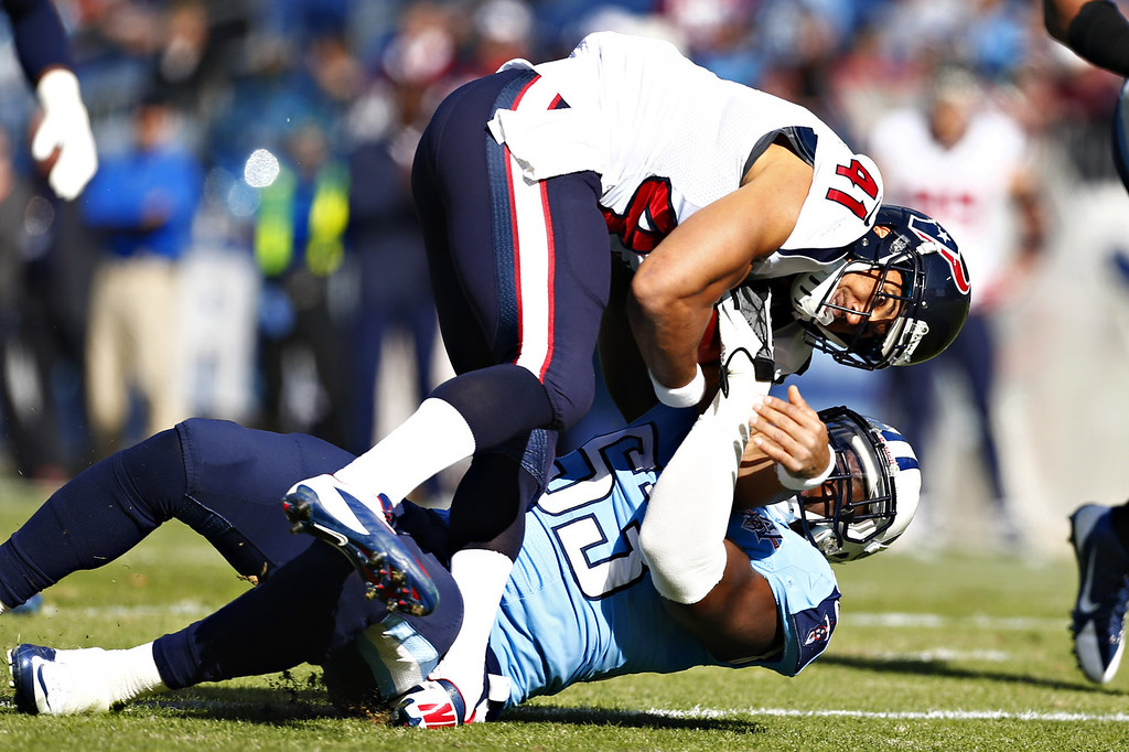 . Jonathan Grimes #41 of the Houston Texans is tackled by Zach Brown #55 of the Tennessee Titans at LP Field on December 29, 2013 in Nashville, Tennessee.  (Photo by Wesley Hitt/Getty Images)