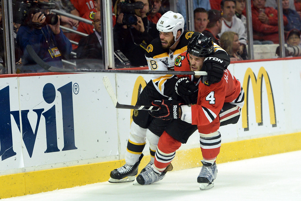 . CHICAGO, IL - JUNE 15:  Nathan Horton #18 of the Boston Bruins holds Niklas Hjalmarsson #4 of the Chicago Blackhawks as they skate behind the net in Game Two of the NHL 2013 Stanley Cup Final at United Center on June 15, 2013 in Chicago, Illinois.  (Photo by Harry How/Getty Images)