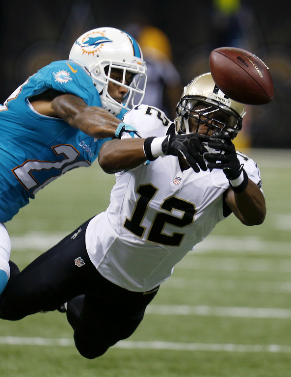 . Miami Dolphins cornerback Nolan Carroll (28) breaks up a pass intended for New Orleans Saints wide receiver Marques Colston (12) in the first half of an NFL football game in New Orleans, Monday, Sept. 30, 2013. (AP Photo/Bill Haber)