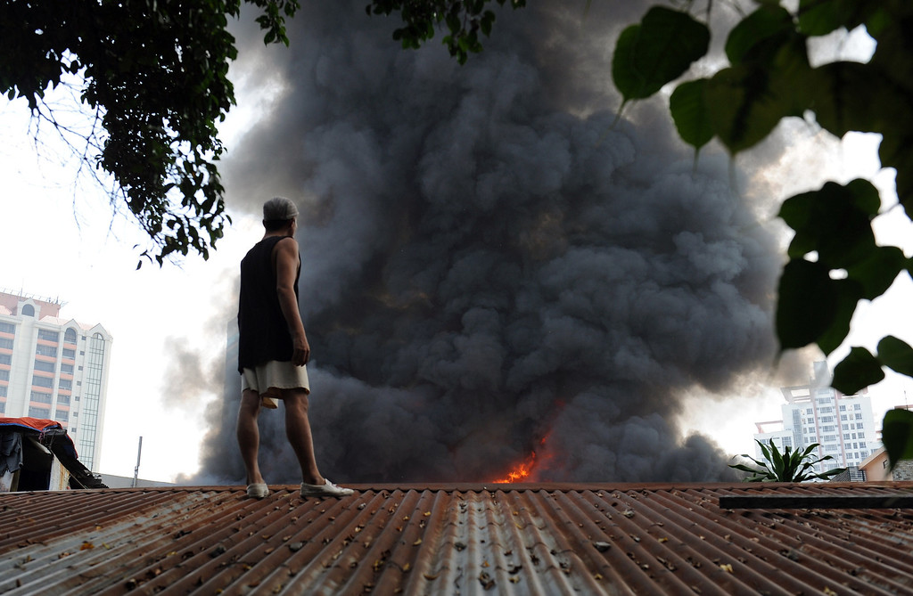 . A resident standing on the roof of his house looks at a fire engulfing a shanty town at the financial district of Manila on July 11, 2013, leaving more than 1,000 people homeless according to city officials. There were no immediate reports of casualties from the blaze, which occurred mid-morning amid government plans to relocate thousands of families living in areas vulnerable to floods and typhoons. TED ALJIBE/AFP/Getty Images