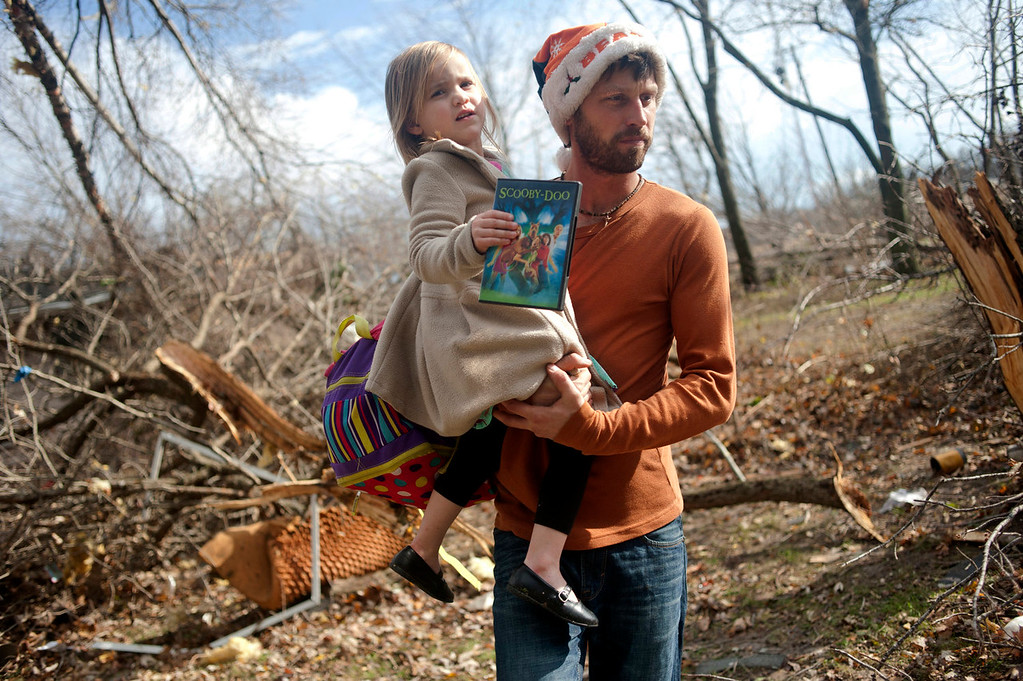 . East Peoria resident Billy Vestal evacuates with his daughter, Lillian Vestal, 3, after a tornado damaged the area near Chestnut Road in East Peoria, Il.,Sunday, Nov. 17, 2013. Intense thunderstorms and tornadoes swept across the Midwest on Sunday, causing extensive damage in several central Illinois communities while sending people to their basements for shelter. (AP Photo/Journal Star, Justin Wan)