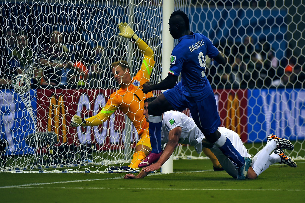 . Italy\'s forward Mario Balotelli scores a goal as England\'s goalkeeper Joe Hart (L) fails to save the ball during a Group D football match between England and Italy at the Amazonia Arena in Manaus during the 2014 FIFA World Cup on June 14, 2014.  AFP PHOTO / FABRICE COFFRINI