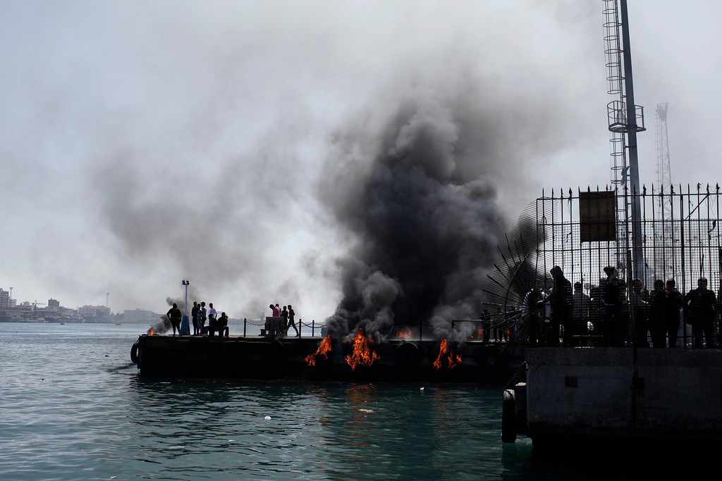. Smoke rises from fires set by protestors in an attempt to block boats from docking and disrupt traffic at the port on the Suez Canal to demonstrate after the announcement of the final verdict in the case of the Port Said football massacre, on March 9, 2013, in Port Said, Egypt. (Photo by Ed Giles/Getty Images).