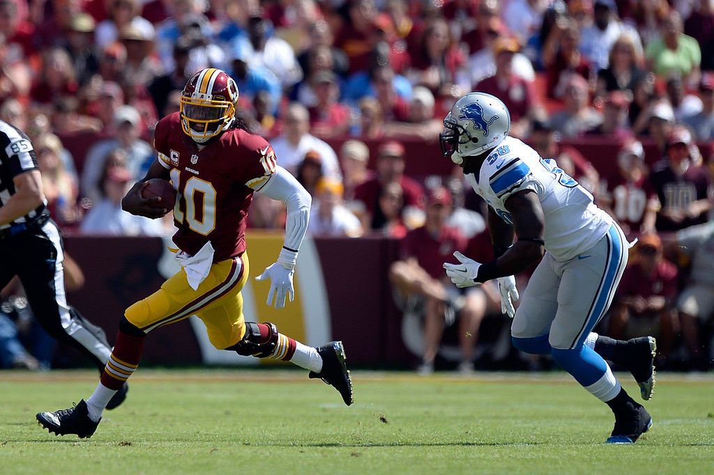 . Robert Griffin III #10 of the Washington Redskins scrambles with the ball as he is chased by Ashlee Palmer #58 of the Detroit Lions in the first quarter during a game at FedExField on September 22, 2013 in Landover, Maryland.  (Photo by Patrick McDermott/Getty Images)