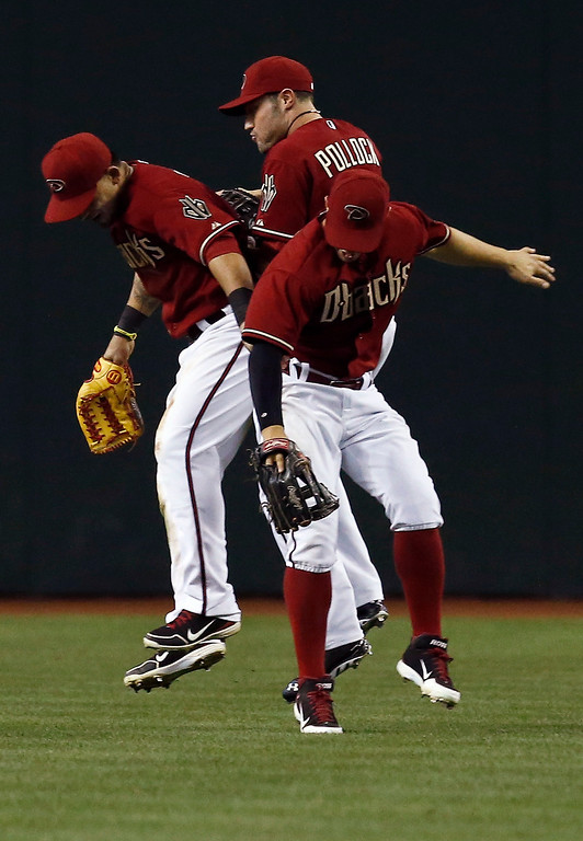 . Arizona Diamondbacks\' Gerardo Parra, left, A.J. Pollock, and Cody Ross, front right, celebrate after the final out in ninth inning of a baseball game against the Colorado Rockies on Sunday, April 28, 2013, in Phoenix. The Diamondbacks defeated the Rockies 4-2. (AP Photo/Ross D. Franklin)