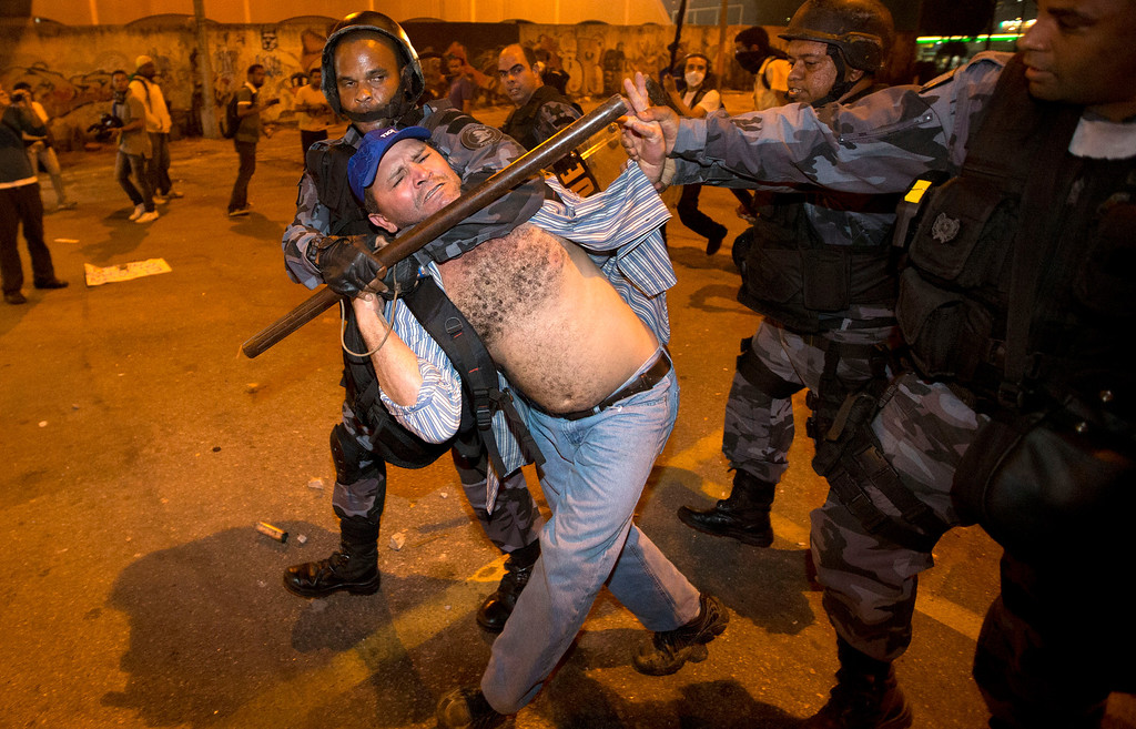 . Military police detain a man during an anti-government protest in Rio de Janeiro, Brazil, Thursday, June 20, 2013. Police and protesters fought in the streets into the early hours Friday in the biggest demonstrations yet against a government viewed as corrupt at all levels and unresponsive to its people.  (AP Photo/Victor R. Caivano)