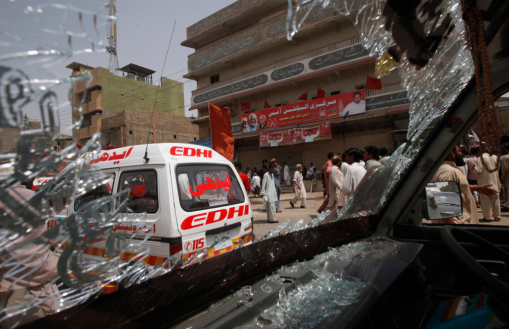. Security officials and residents are seen through the shattered windscreen of a damaged vehicle at the site of a bomb attack in Karachi May 11, 2013. A bomb attack on the office of the Awami National Party (ANP) in the commercial capital, Karachi, killed 11 people and wounded 35. At least two were wounded in a pair of blasts that followed and media reported gunfire in the city. REUTERS/Athar Hussain