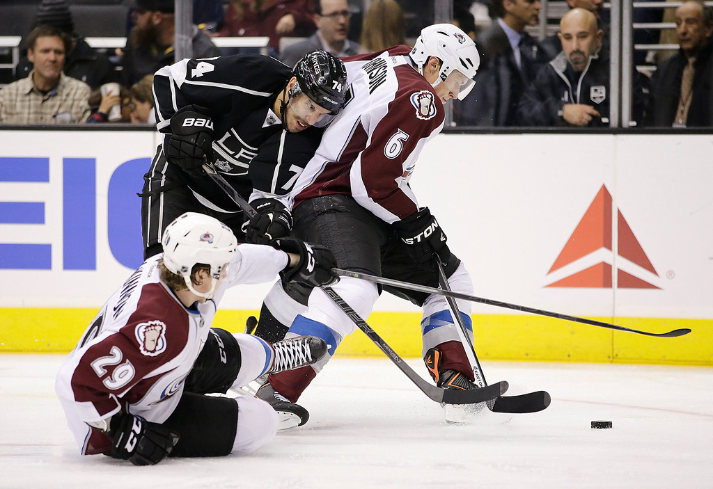 . Los Angeles Kings\' Dwight King, left, fights for the puck with Colorado Avalanche\'s Erik Johnson, right, and Nathan MacKinnon during the second period of an NHL hockey game on Saturday, Nov. 23, 2013, in Los Angeles.(AP Photo/Jae C. Hong)