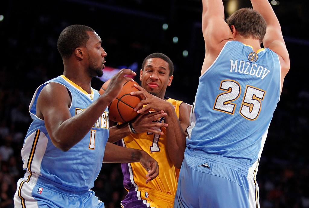 . Los Angeles Lakers guard Xavier Henry, center, collides into Denver Nuggets center Timofey Mozgov (25), of Russia, with Nuggets guard Jordan Hamilton, left, defending during an NBA preseason basketball game Sunday, Oct. 6, 2013 in Los Angeles.  (AP Photo/Alex Gallardo)