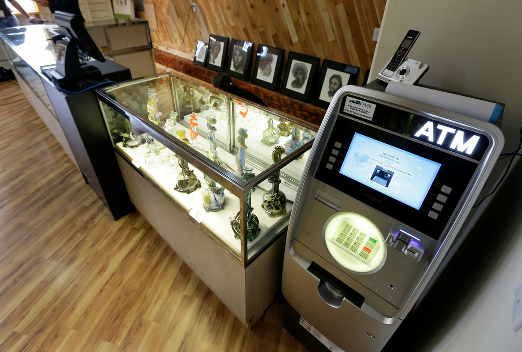 . An ATM sits next to a case displaying glass bongs, Monday, July 7, 2014 at the recreational marijuana store Cannabis City in Seattle. (AP Photo/Ted S. Warren)