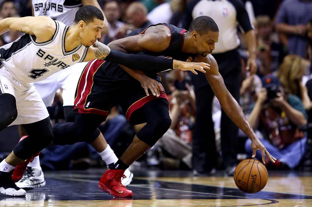 . SAN ANTONIO, TX - JUNE 15: Chris Bosh #1 of the Miami Heat and Danny Green #4 of the San Antonio Spurs battle for a loose ball during Game Five of the 2014 NBA Finals at the AT&T Center on June 15, 2014 in San Antonio, Texas. NOTE TO USER: User expressly acknowledges and agrees that, by downloading and or using this photograph, User is consenting to the terms and conditions of the Getty Images License Agreement.  (Photo by Andy Lyons/Getty Images)