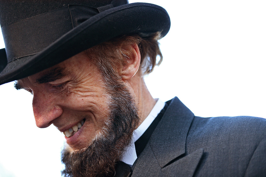 ". Portraying U.S. President Abraham Lincoln, Tom Scott, talks to visitors during a commemoration of the 150th Anniversary of the Gettysburg Address at the Soldiers\' National Cemetery at Gettysburg National Military Park on November 19, 2013 in Gettysburg, Pennsylvania. The iconic Gettysburg Address was given by U.S. President Abraham Lincoln in 1863 during the Civil War and highlighted the principles of democracy, human equality, and freedom and professed that ""government of the people, by the people, for the people, shall not perish from the earth.\"" (Photo by Patrick Smith/Getty Images)"