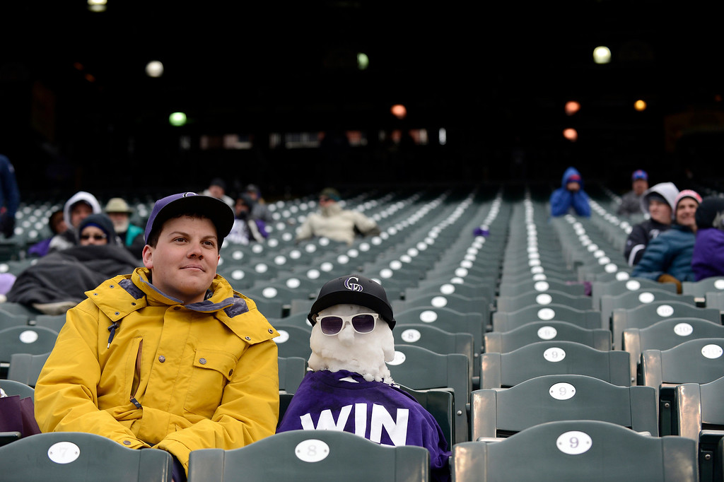 . Andrew Tollerud of Lakewood enjoys the Colorado Rockies New York Mets game with a snowman he built to sit next to April 16, 2013 at Coors Field. The Rockies grounds crew had to clear of 8 inches of snow from the field to get it ready for a double header with the Mets.  (Photo By John Leyba/The Denver Post)
