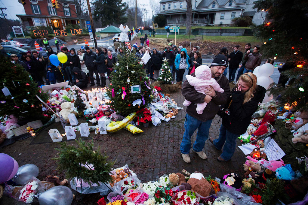 . A family embraces while visiting a memorial to the victims of the recent school shooting in Sandy Hook Village in Newtown, Connecticut, December 16, 2012. Worshippers filled Sunday services to mourn the victims of a gunman\'s elementary school rampage that killed 20 children and six adults with President Barack Obama due to appear later at an interfaith vigil to help this shattered Connecticut town recover.  REUTERS/Lucas Jackson