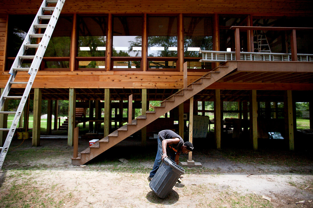 . Kyle Alexander, 20, cleans up the yard while working on the construction site of a new vacation home being built for a couple from the Northeast, in the Hog Hammock community of Sapelo Island, Ga. on Thursday, May 16, 2013. (AP Photo/David Goldman)