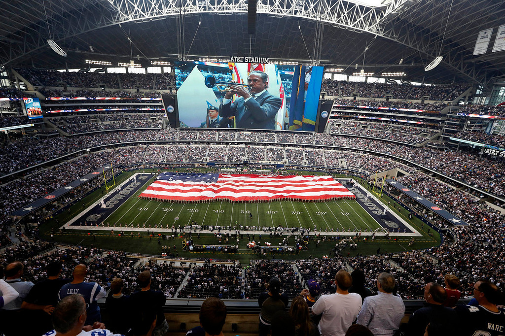 . An American flag is unfurled over the field during the playing of the national anthem at the start of an NFL football game between the Minnesota Vikings and Dallas Cowboys, Sunday, Nov. 3, 2013, in Arlington, Texas. (AP Photo/Sharon Ellman)