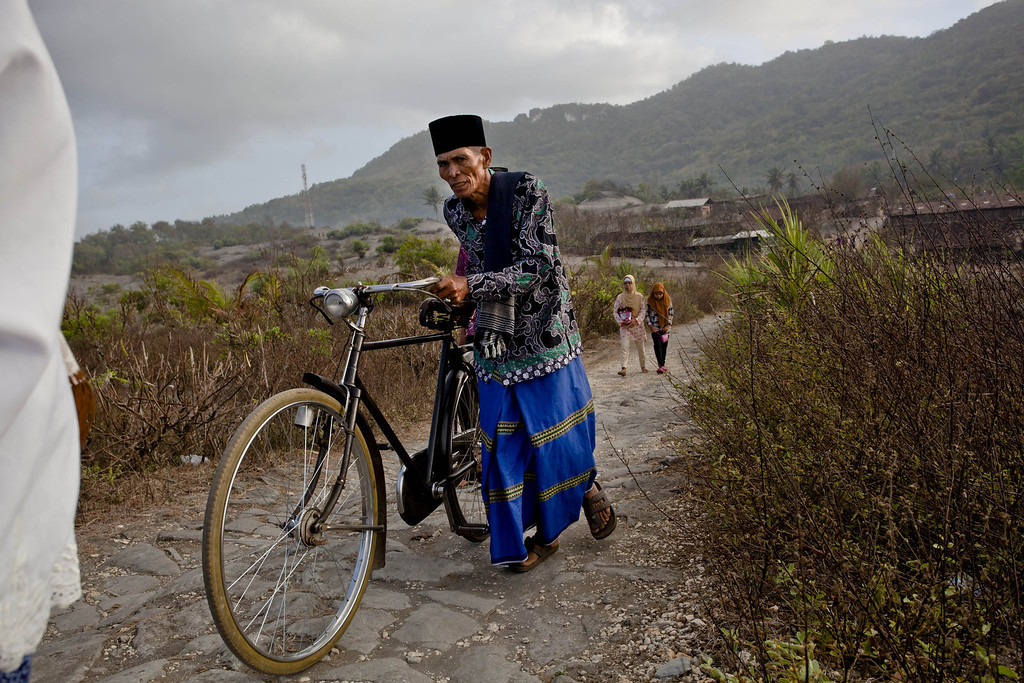 . An Indonesian muslim man walks with his bicycle on \'sea of sands\' as they prepare for Eid Al-Adha prayer at Parangkusumo beach  on October 15, 2013 in Yogyakarta, Indonesia. (Photo by Ulet Ifansasti/Getty Images)