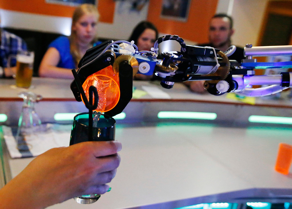 """. Humanoid robot bartender \""""Carl\"""" pours a spirit into the cocktail shaker of a bartender to prepare a drink for a guest at the Robots Bar and Lounge in the eastern German town of Ilmenau, July 26, 2013. \""""Carl\"""", developed and built by mechatronics engineer Ben Schaefer who runs a company for humanoid robots, prepares spirits for the mixing of cocktails and is able to interact with customers in small conversations. Picture taken July 26, 2013. REUTERS/Fabrizio Bensch"""