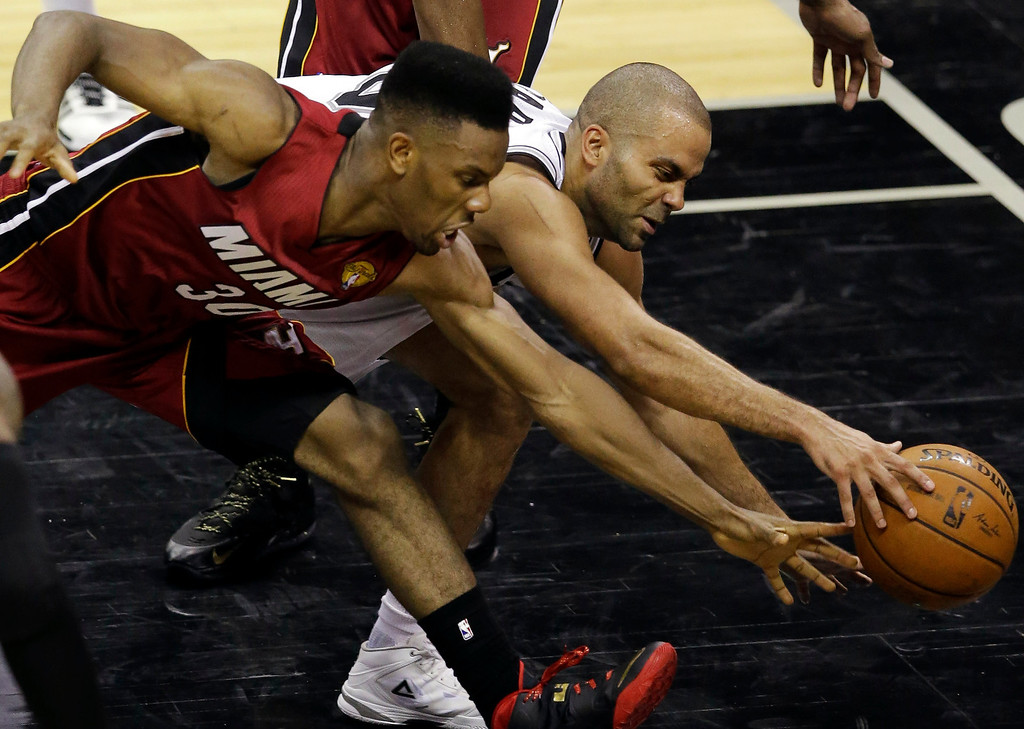 . Miami Heat guard Norris Cole (30) and San Antonio Spurs guard Tony Parker go after a loose ball during the second half in Game 1 of the NBA basketball finals on Thursday, June 5, 2014 in San Antonio. (AP Photo/Tony Gutierrez)