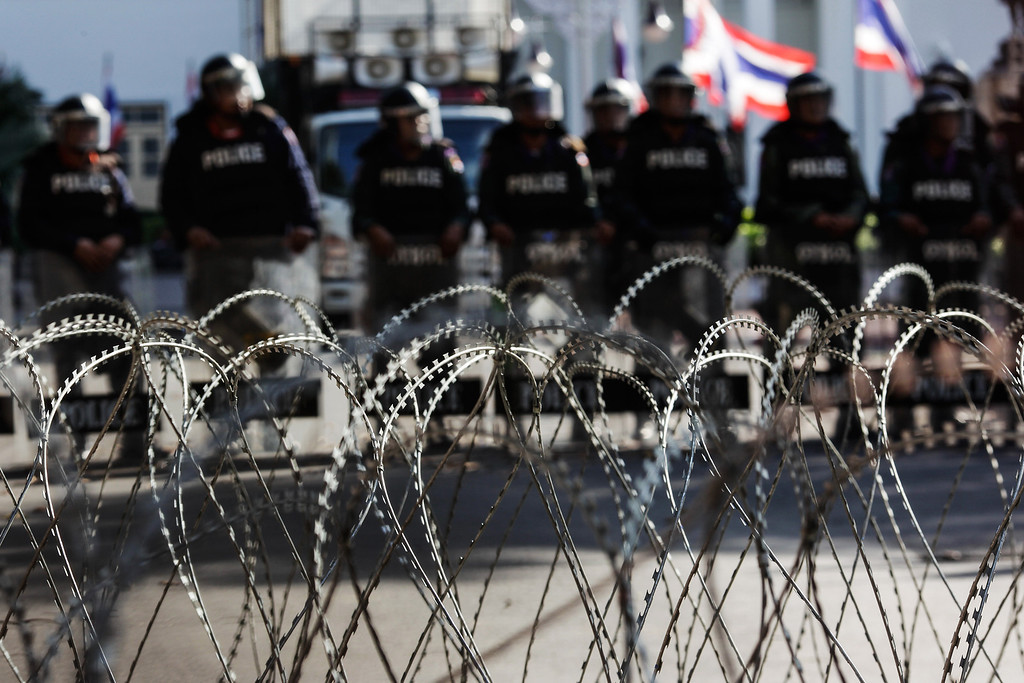 . Riots police officers stand guard behind barbed wire barricades during an anti-government protest outside the police headquarters in Bangkok, Thailand, on Thursday, Nov. 28, 2013. Thai Prime Minister Yingluck Shinawatra, who survived a censure vote in parliament, called on protesters seeking her ouster to end their occupation of government buildings and come to the negotiating table for the good of the country. Photographer: Dario Pignatelli/Bloomberg