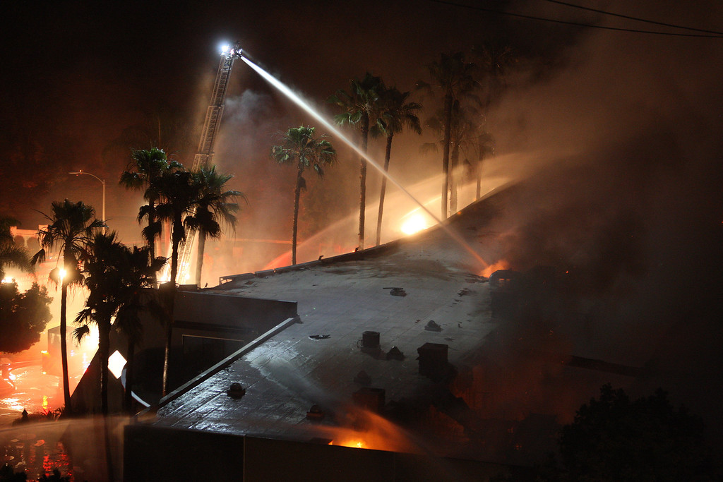 . Firefighters spray water on a burning commercial structure at the Poinsettia fire, one of nine wildfires fueled by wind and record temperatures that erupted in San Diego County throughout the day, on May 14, 2014 in Carlsbad, California.   (Photo by David McNew/Getty Images)