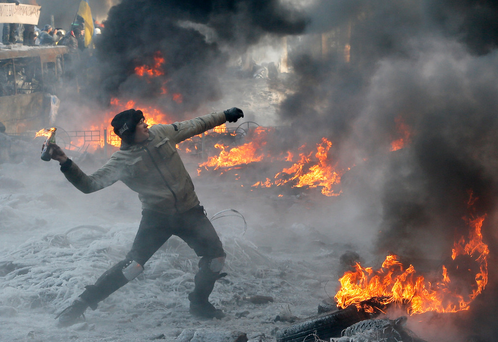 . A protester throws a Molotov cocktail towards riot police during a clash in central Kiev, Ukraine, Saturday Jan. 25, 2014. Ukraine\'s Interior Ministry has accused protesters in Kiev of capturing two of its officers as violent clashes have resumed in the capital and anti-government riots spread across Ukraine. (AP Photo/Efrem Lukatsky)